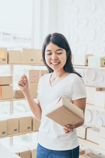 Proprietário de negócios de mulheres asiáticas trabalhando em casa com a caixa de embalagem no local de trabalho Foto Premium