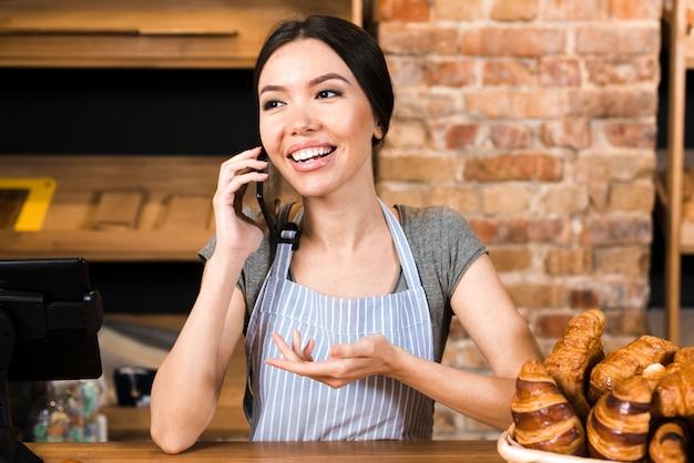 Proprietário de padaria feminino no balcão com croissant falando no celular Foto gratuita