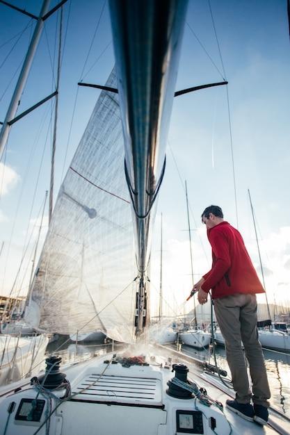 Proprietário de veleiro ou iatista usa mangueira para lavar água salgada do convés do iate quando atracado ou estacionado na marina ao pôr do sol Foto gratuita