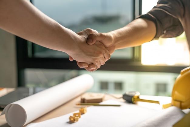 Proprietário e construtor está de acordo e apertar as mãos para comemorar no sucesso do acabamento no projeto de construção de contrato de construção de casa Foto Premium