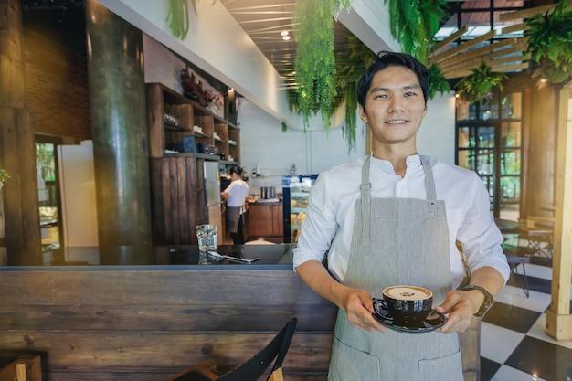 Proprietário empresarial bem sucedido bonito que está com uma xícara de café na frente da barra. Foto Premium