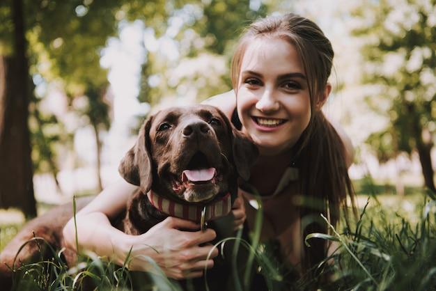 Proprietário está sorrindo e abraçando seu animal de estimação em madeira verde. Foto Premium