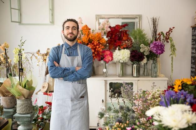 Proprietário masculino da loja de flor que olha confiantemente na câmera Foto gratuita