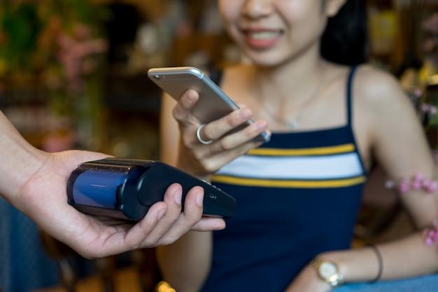 Proprietário usando a máquina de pagamento para receber o smartphone do cliente de forma de dinheiro Foto Premium