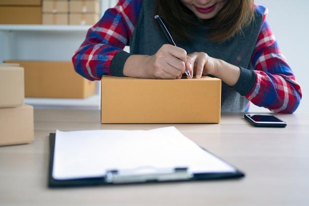 Proprietários de pequenas empresas estão escrevendo nomes para se preparar para entregar pacotes aos clientes. pequenas empresas que vendem on-line e encomendam produtos on-line Foto Premium
