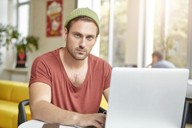 Próspero jovem gerente usa camiseta casual e chapéu, trabalha em um laptop genérico Foto gratuita