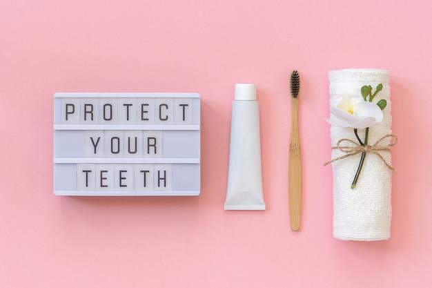 Proteja seu texto dentes na caixa de luz e escova de bambu natural eco-friendly para dentes, toalha, tubo de creme dental. Foto Premium