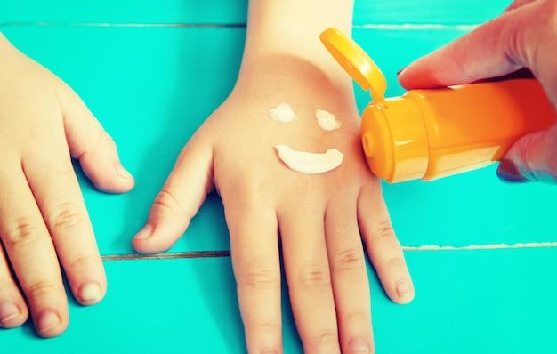 Protetor solar na mão de uma criança. Foto Premium
