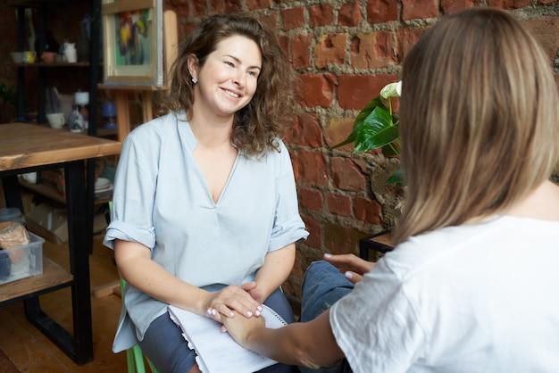 Psicóloga segurando a mão de uma mulher Foto Premium