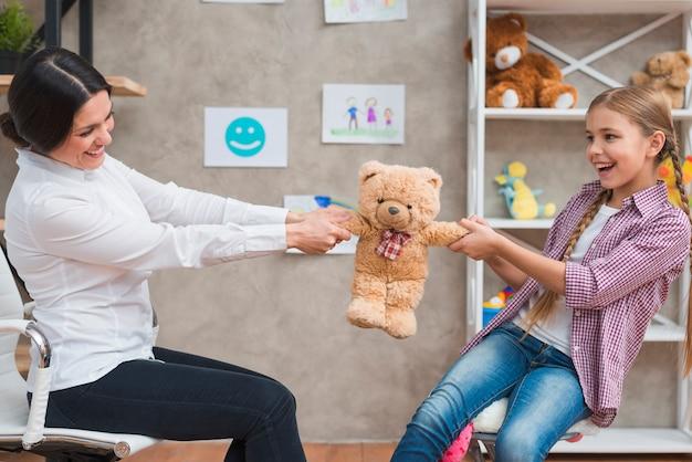 Psicólogo feminino, e, menina sorridente, sentando, cara enfrentar, puxando, a, teddybear Foto gratuita