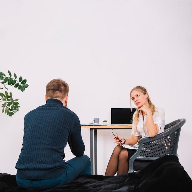 Psicólogo feminino seriamente ouvindo o paciente no escritório Foto gratuita