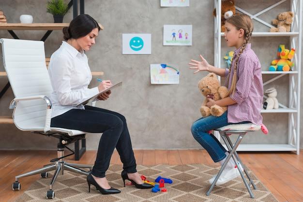 Psicólogo feminino tomando notas durante a sessão de terapia Foto gratuita