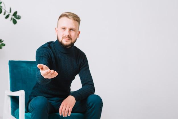 Psicólogo masculino, estendendo a mão amiga na câmera para aperto de mão contra parede branca Foto gratuita