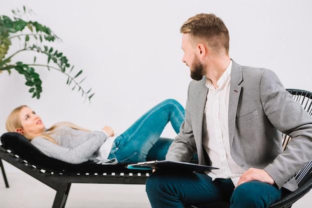 Psicólogo masculino, olhar, dela, femininas, paciente, mentindo sofá Foto gratuita