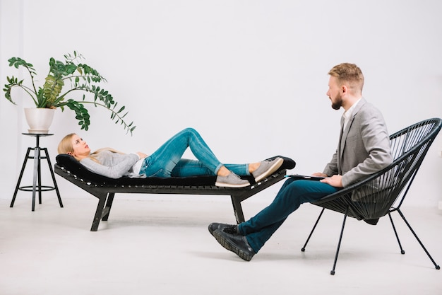 Psicólogo profissional, conduzindo a consulta feminina deitado no sofá Foto gratuita