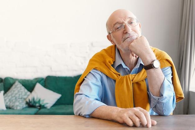 Psicólogo sênior careca com óculos retangulares e suéter amarrado nos ombros, sentado na mesa de madeira vazia do escritório em casa, esperando pelo cliente, com expressão facial atenciosa Foto gratuita