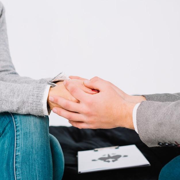 Psicólogo, sentando, e, toque, mão, de, jovem, mulher deprimida, para, encorajamento Foto gratuita