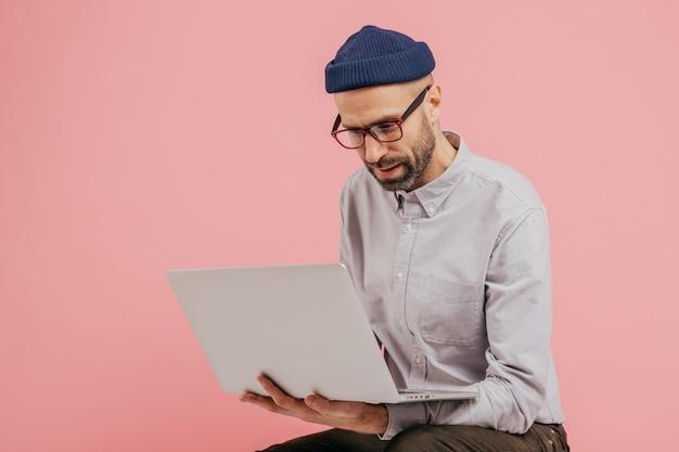 Publicador de tipos bem-sucedido de redatores, lê informações, segura um computador laptop, usa óculos Foto Premium