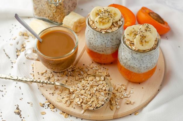 Pudim caseiro da semente do chia com banana, refeições frescas desidratadas do abricó e da aveia e café na placa de madeira com espaço da cópia. Foto Premium