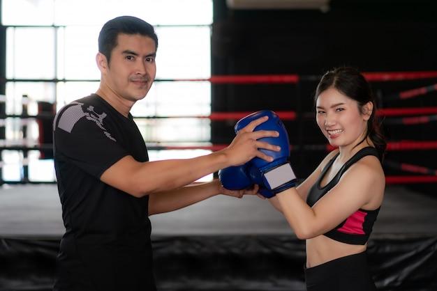 Pugilista asiático novo da mulher com pose profissional do instrutor e sorriso na câmera durante o treinamento. Foto Premium