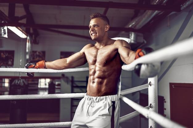 Pugilista profissional musculoso descansando nas cordas no canto do ringue enquanto treinava para a próxima partida Foto Premium