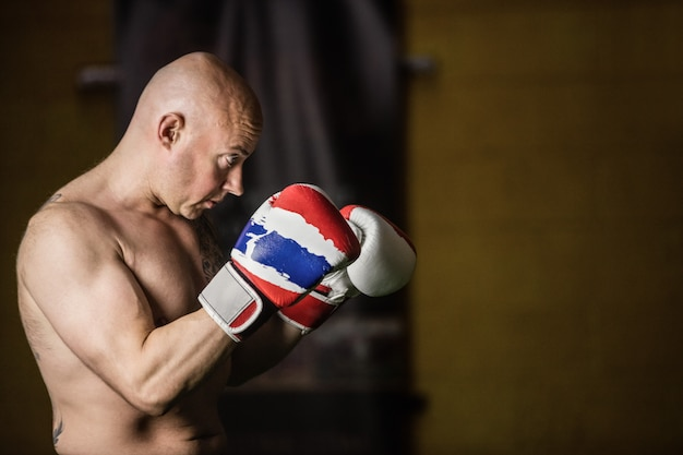 Pugilista tailandês praticando boxe Foto gratuita