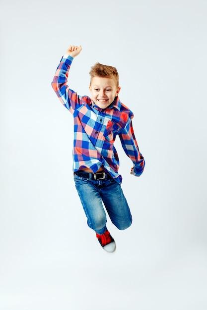 Pulando menino de camisa xadrez colorida, jeans azul, sapatos desportivos. isolado. Foto Premium
