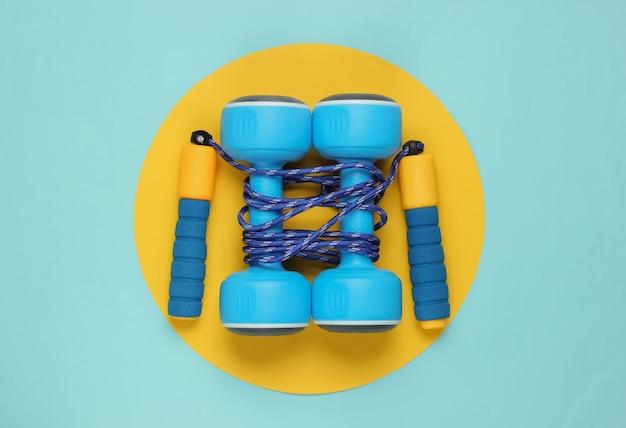 Pular corda enrolada em halteres em amarelo azul pastel Foto Premium
