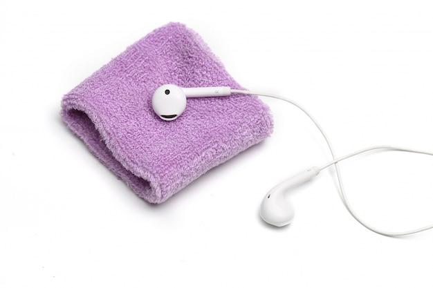 Pulseira de algodão e fone de ouvido no fundo branco Foto gratuita