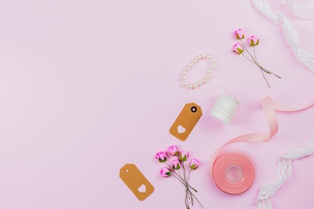 Pulseira de pérolas; tag; fita; carretel de linha; rendas e rosas artificiais no pano de fundo rosa Foto gratuita