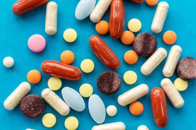Punhado de pílulas coloridas derramadas fora da lata Foto Premium