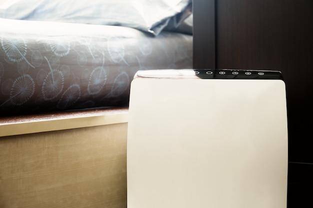 Purificador de ar no limpador de quarto de cama removendo poeira fina em casa. Foto Premium