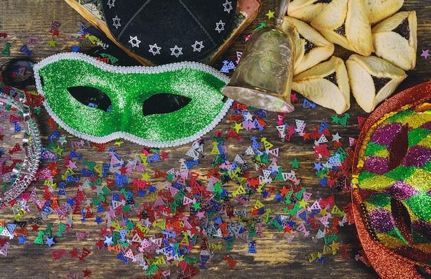 Purim feriado judaico com purim máscara e purim um noisemaker em um fundo de madeira vintage com copys ritmo Foto Premium