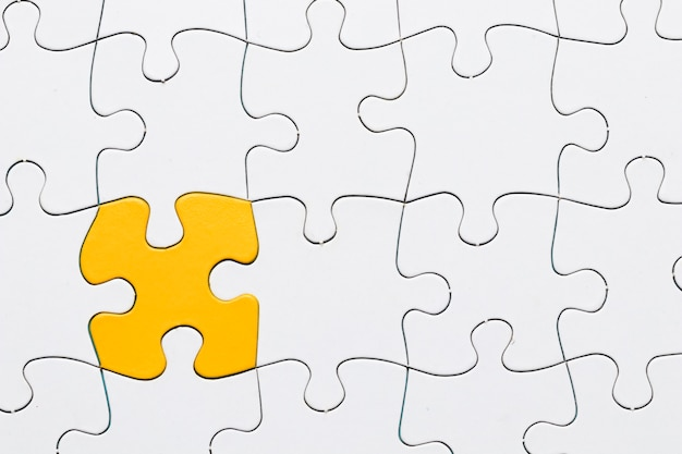 Puzzle amarelo entre grade de quebra-cabeça branca Foto gratuita