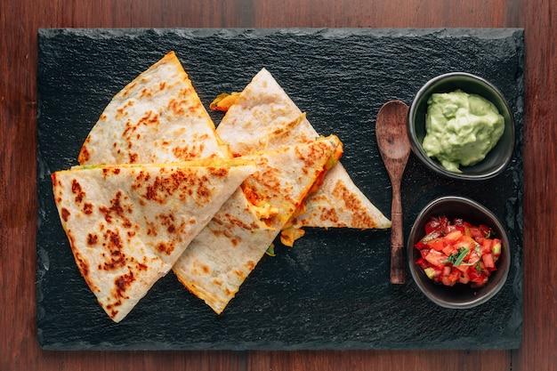 Qu quesadillas de frango e queijo assadas servidas com salsa e guacamole no prato de pedra. Foto Premium