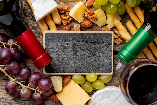 Quadro ao lado de garrafas de vinho e uva e queijo Foto gratuita
