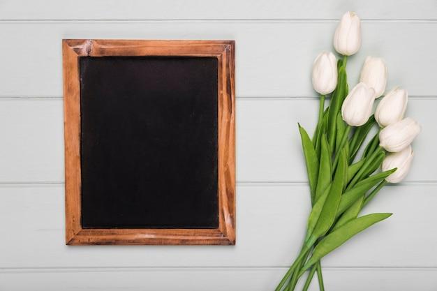 Quadro ao lado de tulipas brancas na mesa Foto gratuita