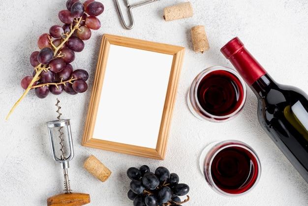 Quadro ao lado de uvas e garrafa de vinho Foto gratuita