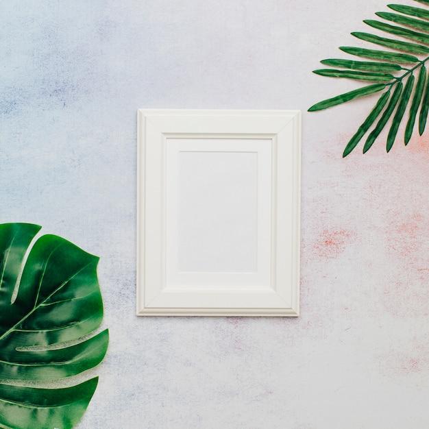 Quadro bonito branco com folhas tropicais Foto gratuita