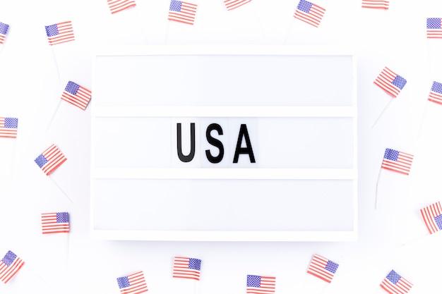 Quadro branco com nota eua cercado por pequenas bandeiras americanas Foto gratuita