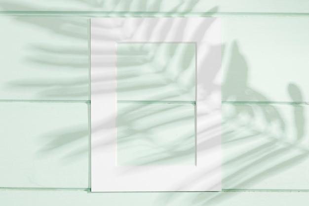 Quadro branco vertical com sombra de folha Foto gratuita