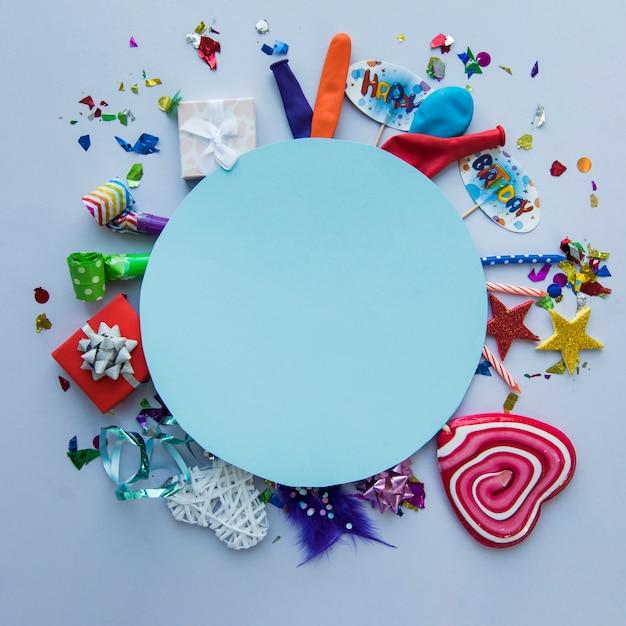 Quadro circular azul em branco sobre os itens de festa de aniversário no fundo Foto gratuita