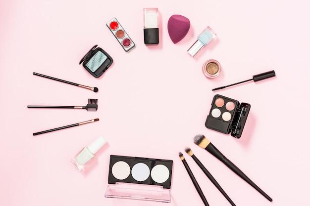 Quadro circular feito com pincéis de maquiagem; garrafa de esmalte; sombra; liquidificador no fundo rosa Foto gratuita
