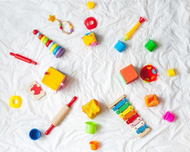 Quadro colorido brilhante dos brinquedos das crianças no fundo branco. vista do topo. lay plana. copie o espaço para te Foto Premium