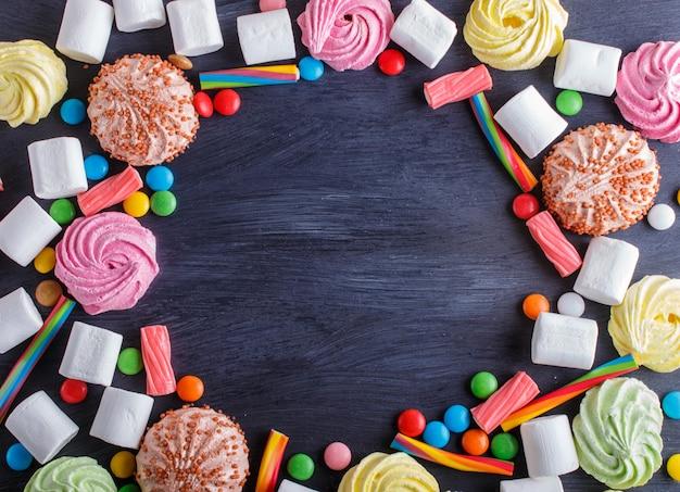 Quadro colorido de doces coloridos no fundo de madeira preto. Foto Premium