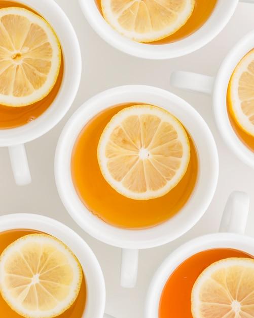 Quadro completo de chá de ervas de limão em copos em pano de fundo branco Foto gratuita