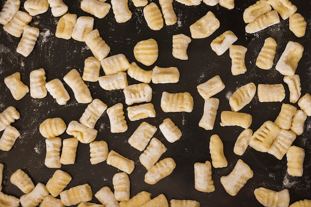 Quadro completo de nhoque de massas caseiras não cozidas na bancada da cozinha Foto gratuita