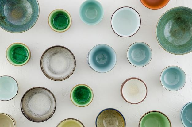 Quadro completo de tigelas de cerâmica e de vidro e xícaras de chá no fundo branco Foto gratuita