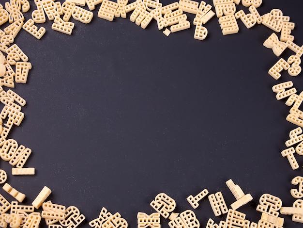 Quadro de alfabeto de macarrão cru em fundo preto Foto Premium