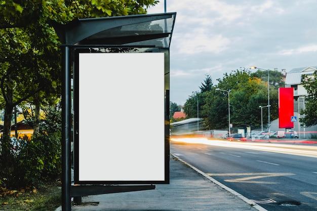 Quadro de avisos no abrigo de ônibus com luz de trilha turva Foto gratuita